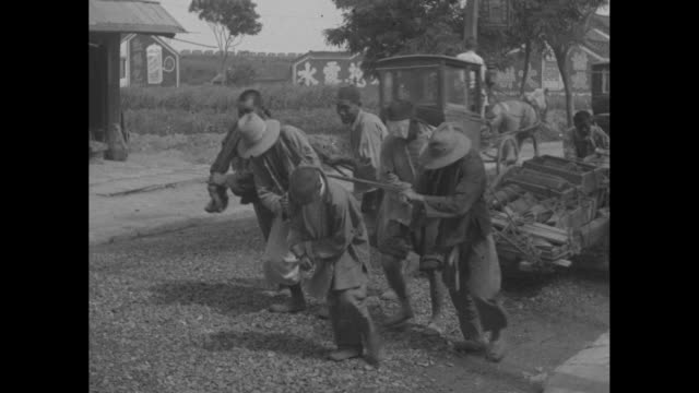 several chinese men push and pull a heavy cart loaded with supplies / note exact month/day not known - push cart stock videos & royalty-free footage