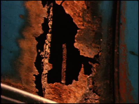 / Several closeup shots of rusty fenders doors and hoods / Narrator talks about Studebaker's rustproofing process at the factory / Worker spot welds...