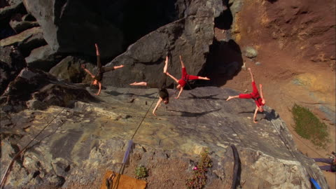 several dancers suspended by wires dance on the face of a cliff. available in hd. - klippe stock-videos und b-roll-filmmaterial