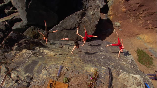 several dancers suspended by wires dance on the face of a cliff. available in hd. - werfen stock-videos und b-roll-filmmaterial
