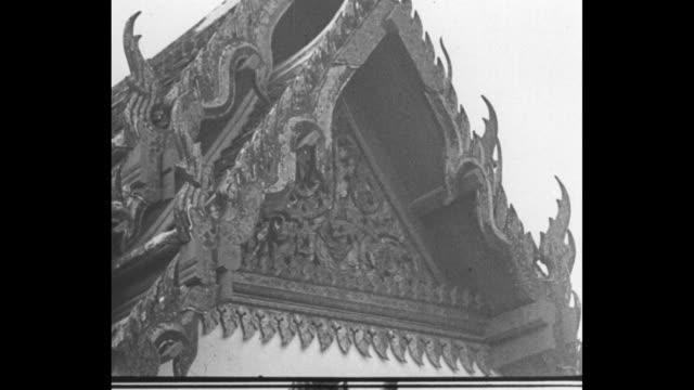 DOWN several domeshaped stupa structures tall spires / MLS man walks between stupas / CU ornate decor above entrance to building / TILT UP novice boy...