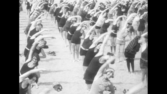 several dozen people, mostly women, on brooklyn's brighton beach perform arm exercises / exercisers do side stretches / women seated on sand touch... - sit ups stock videos & royalty-free footage
