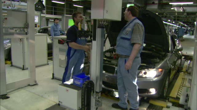 Several employees work at various assembly lines in a BMW factory.