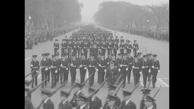 several groups of soldiers parade past the east front of the united states capitol with a crowd looking on teams of white horses pull caissons / the... - pennsylvania avenue video stock e b–roll