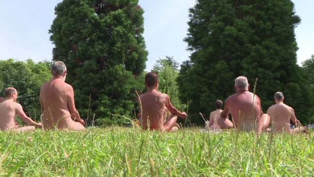 stockvideo's en b-roll-footage met several hundred nudists gather in the bois de vincennes for yoga and a picnic in the nude in honor of naturism day in paris - naturist
