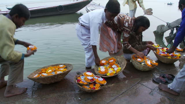 Several Indian children making floating candles.