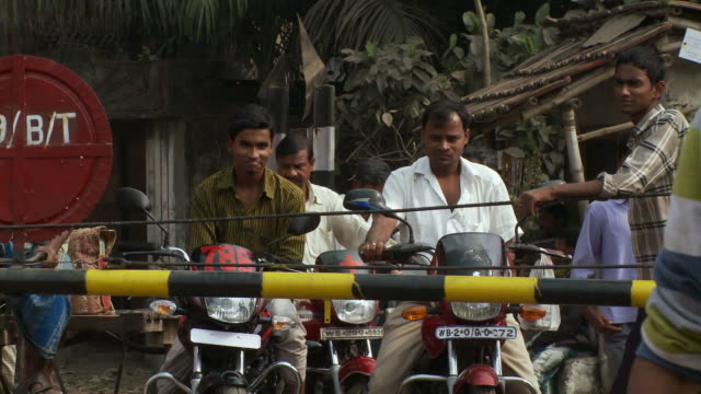 several indian men waiting on motorcycles. - boom barrier stock videos & royalty-free footage