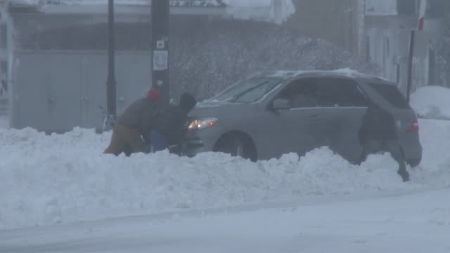 Several men do their best to help dig out and then push a vehicle stuck in deep snow in Freehold NJ during the Blizzard of 2016