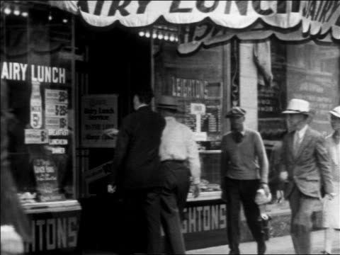 b/w 1930 several men entering diner from busy city sidewalk / los angeles, ca - 1930点の映像素材/bロール