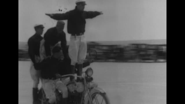several men in numerous athletic poses riding on motorcycles and a sidecar with spectators and numerous ford model a automobiles just beyond / note:... - sidecar stock videos & royalty-free footage