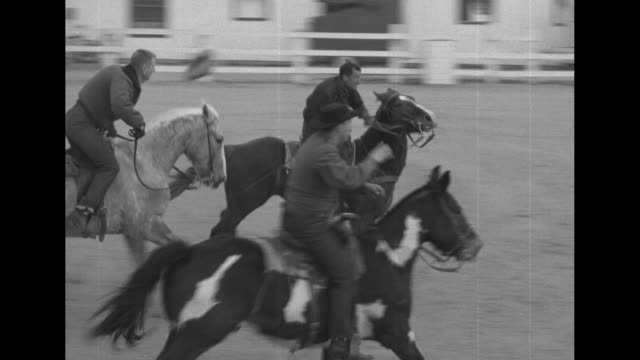 VS several men on horseback gallop back and forth with a basketball in a dusty corral with hoops Apple Valley Ranchos / The ball rolls into the frame...