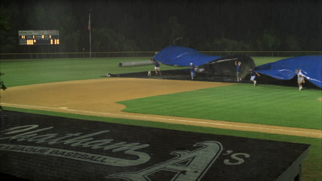 ws pan several men pulling large tarp over baseball diamond - 防水シート点の映像素材/bロール