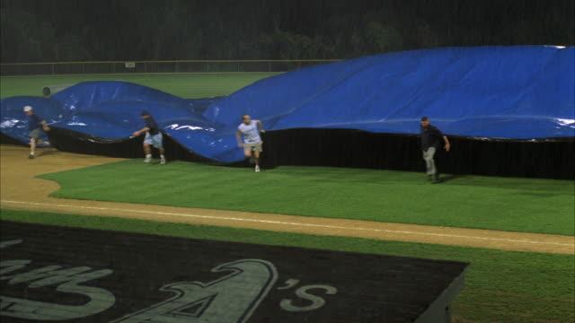 vidéos et rushes de ws pan several men pulling large tarp over baseball diamond - terrain de sport sur gazon
