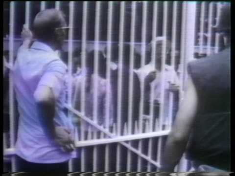 several men talk to a group of vietnamese people behind the embassy gates. - (war or terrorism or election or government or illness or news event or speech or politics or politician or conflict or military or extreme weather or business or economy) and not usa stock videos & royalty-free footage