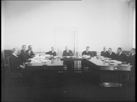 several men wait in a meeting room / press photographers shoot the scene / secretary of labor frances perkins sits at a table with other men / eugene... - sozialversicherung stock-videos und b-roll-filmmaterial