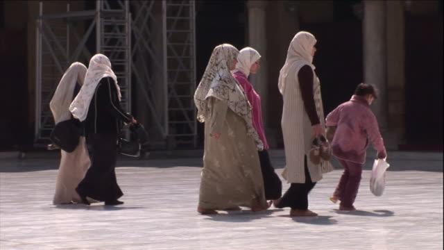vidéos et rushes de several muslim women chat as they walk across a plaza. - islam