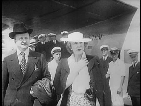 several newsreel cameramen photograph alfred duff-cooper and lady diana in front of the water / duff-cooper and diana walk with john julius cooper /... - 水上飛行機点の映像素材/bロール