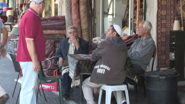 stockvideo's en b-roll-footage met several older men getting up from a small table on the sidewalk in the old town - jaffa