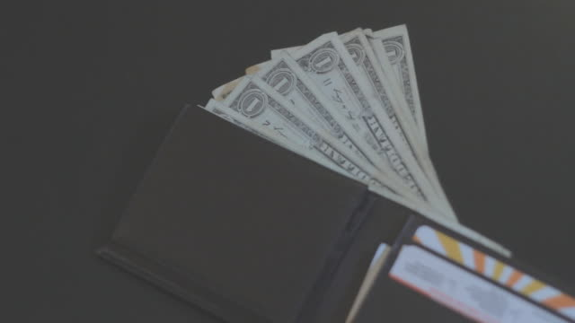 Several one dollar bills sticking out of wallet flat on dark surface, side view.