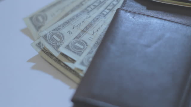 Several one dollar bills sticking out of wallet flat on white surface, side view.