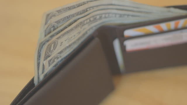 Several one dollar bills sticking out of wallet standing up on dark surface.