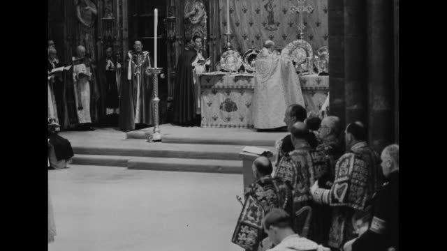 several peers standing in front of king edward's chair / archbishop of canterbury at altar turns around holding sword of state and carries it to... - coronation stock videos and b-roll footage