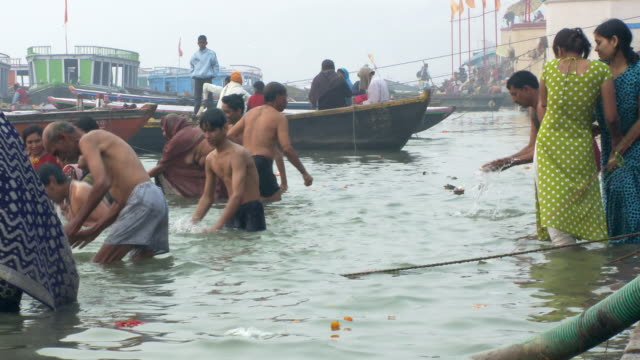 Several people bathing in the Ganges river.