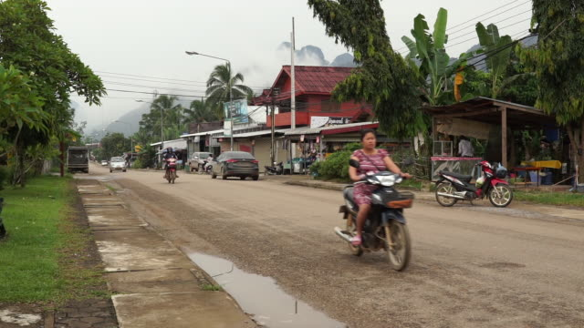 several people driving on street in vang vieng laos - developing countries stock videos & royalty-free footage