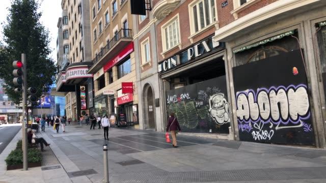 vídeos y material grabado en eventos de stock de several people walk through the door of the old rex cinema and a closed fashion store on madrid's gran via on september 29, 2020 in madrid, spain.... - lugar de comercio