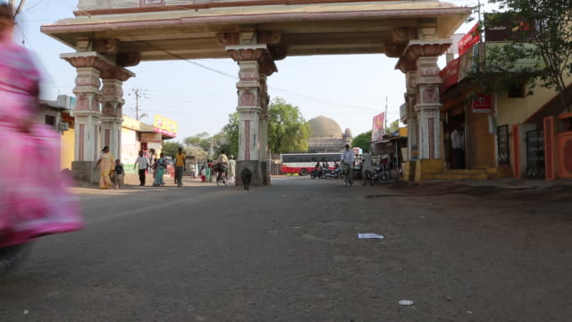 ws of several people walking by on a large town square with two large pillars that are visible on march 29 2013 in bijapur india in the background... - mausoleum stock videos and b-roll footage
