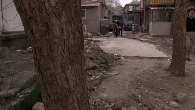 ws pan several people walking through alley past rubble near lake houhai, beijing, china - rubble stock-videos und b-roll-filmmaterial