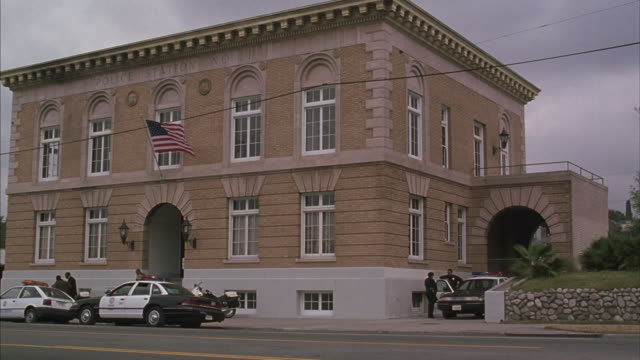 Several police officers leave a Los Angeles Police Station in this establishing shot.