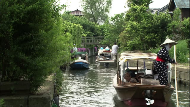 several sappa boats with tourists on board are slowly riding down the creek surrounded by greenery. sightseeing boat passes by an oncoming boat in a... - narrow stock videos & royalty-free footage
