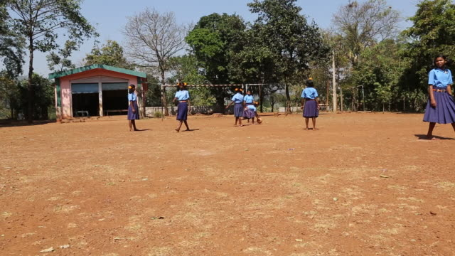WS PAN of several schoolgirls in school uniforms who are playing soccer on a football field at a school in the village Satia a small settlement 300...