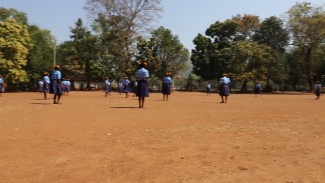 ws pan of several schoolgirls in school uniforms who are playing soccer on a football field at a school in the village satia a small settlement 300... - westbengalen stock-videos und b-roll-filmmaterial