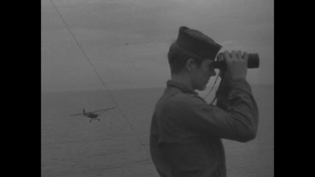 Several shots of US warplanes flying overhead / shot of jungle still occupied by Japanese forces / guns on US warship rotating into firing position /...
