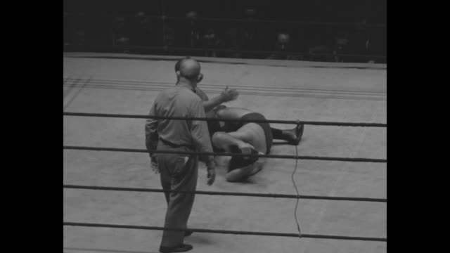 Several shots of wrestlers Floyd Marshall and Serge Kalmikoff during match with body slams punches and takedowns