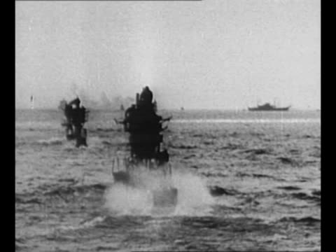 several submarines in atlantic ocean with sailors standing on top of three of them doing wigwag signaling as other us navy ships sail in background... - atlantik stock-videos und b-roll-filmmaterial