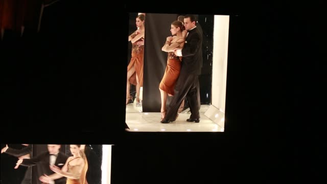 Several tango couples dancing in small cabins which are illuminated An episode of a tango show during the show 'Tango Porteno' in Buenos Aires...