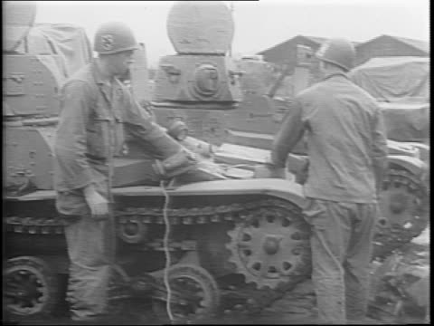 several tanks are parked in a muddy field / soldiers wrap the tanks with wire / soldiers slide sticks of dynamite down the tanks' muzzles / a pair of... - 起爆装置点の映像素材/bロール
