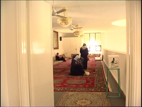 several traditional shia lebanese women are sitting on the carpet in the women's section of a mosque. an open copy of the quran is on the floor in... - shi'ite islam stock videos & royalty-free footage