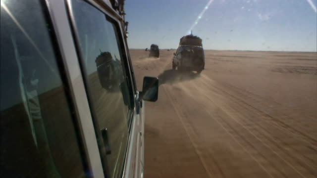 vidéos et rushes de several trucks leave tracks in the sand as they drive over a vast desert. - paysage enchanteur