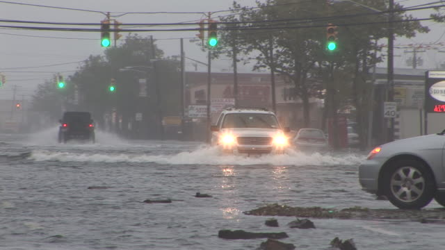 several vehicles risk driving through deep and fast moving flood waters, as others turn around during hurricane irene's landfall in the new york city... - hurricane irene stock videos & royalty-free footage