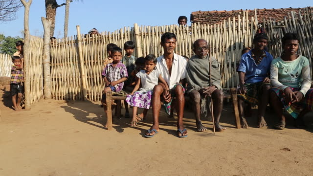 WS PAN of several villagers of various age that are sitting on a wooden bench in a halfcircle in front of a wooden fence made of bamboo canes in a...