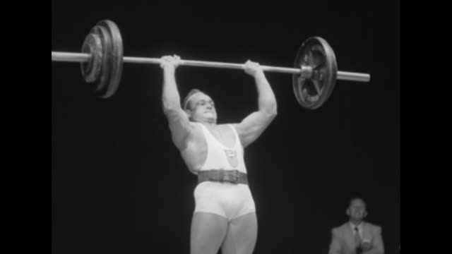 Several weightlifters lift free weights onstage