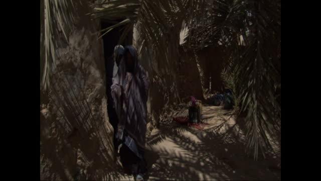 several women in traditional full-length burkas exit through the doorway of a hut. - モデスト・ファッション点の映像素材/bロール