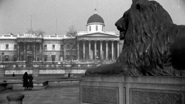 several women look out at the national art gallery as they stand near a lion statue at trafalgar square. - 1936 stock videos & royalty-free footage