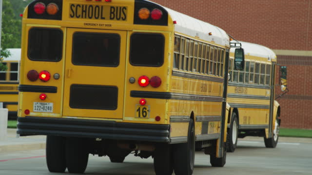 Several yellow school buses drive away from camera after delivering children to school early in the morning.