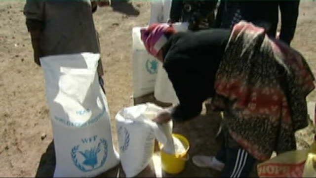 severe drought blamed on global warming lesotho ext sack of food aid being carried away people waiting for aid flour being scooped from sack into... - jug stock videos & royalty-free footage