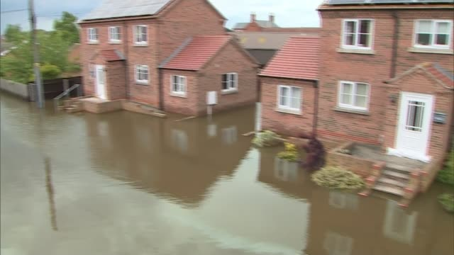 severe flooding forces evacuation in wainfleet lincolnshire england lincolnshire wainfleet ext floodwater around houses woman wading across flooded... - lincolnshire stock videos & royalty-free footage